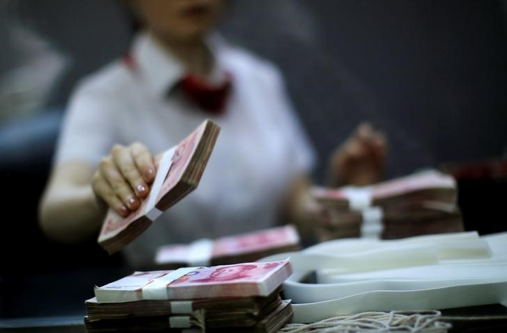 © Reuters. FILE PHOTO: Employee of the Industrial and Commercial Bank of China Ltd counts money at one of the bank's branches at the Shanghai Free Trade Zone in Pudong district, in Shanghai