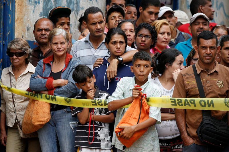 © Reuters. People look at police officers and criminal investigators while they collect evidence in front of a bakery, after it was looted in Caracas
