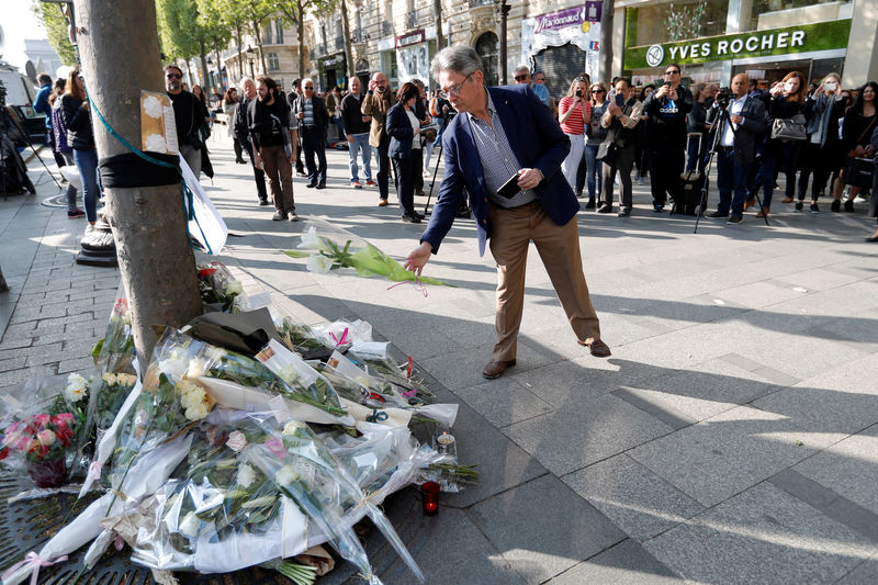 © Reuters. A man leaves flowers on the Champs Elysees Avenue the day after a policeman was killed and two others were wounded in a shooting incident in Paris