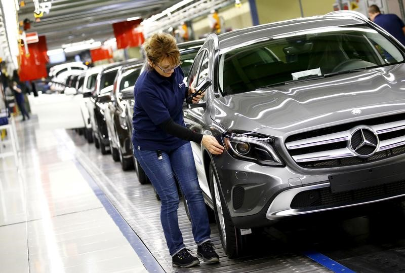 © Reuters. FILE PHOTO: Employees of German car manufacturer Mercedes Benz make final adjustments at the end of the Mercedes A class (A-Klasse) production line at the factory in Rastatt
