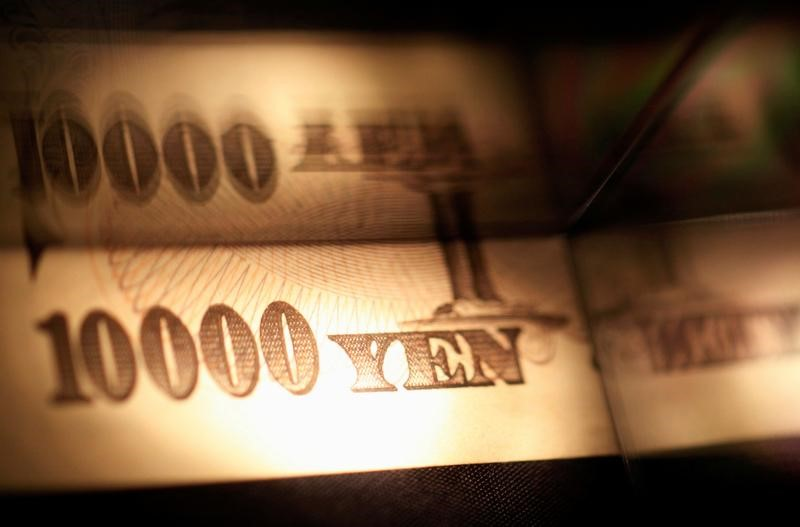 © Reuters. Light is cast on a Japanese 10,000 yen note as it's reflected in a plastic board in Tokyo, in this picture illustration
