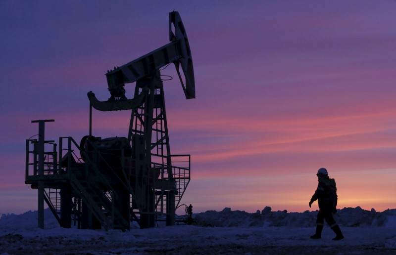 © Reuters. File photo of a worker walking past a pump jack on an oil field owned by Bashneft, Bashkortostan