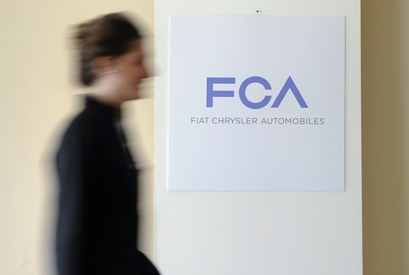 © Reuters. A woman walks past a logo of Fiat Chrysler Automobiles (FCA) in Turin