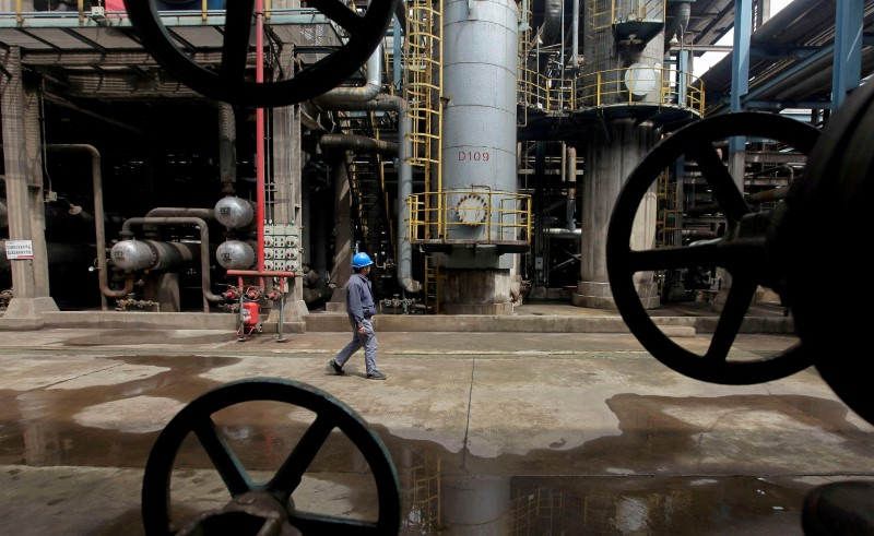 © Reuters. FILE PHOTO: A worker walks past oil pipes at a refinery in Wuhan