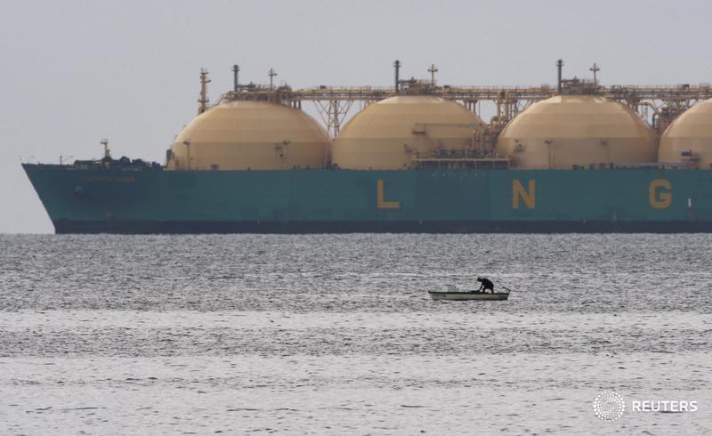 © Reuters. Рыбак раядом с СПГ-танкером близ Гаваны