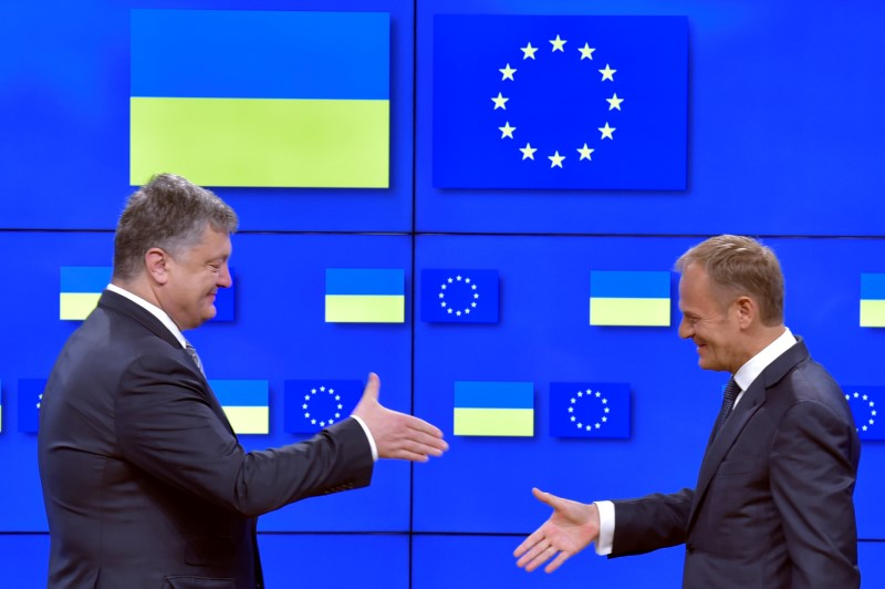 © Reuters. European Council President Tusk shakes hand with Ukrainian President Poroshenko after a joint news conference in Brussels