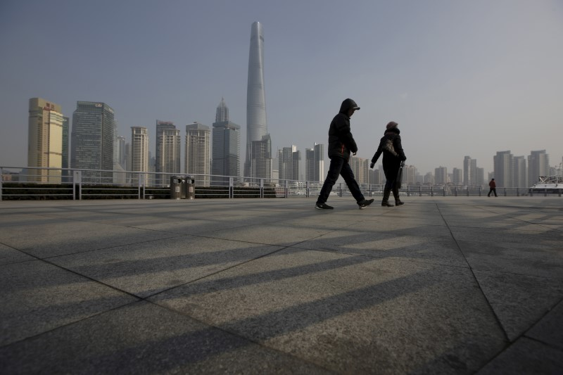© Reuters. People walk in front of the financial district of Pudong in Shanghai