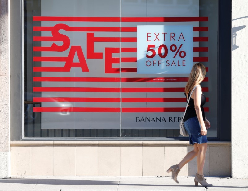© Reuters. A woman walks past a sign advertising a sale in the Old Town shopping area of Pasadena