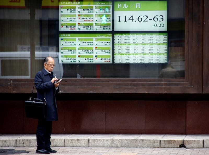 © Reuters. A man stands in front of electronic boards showing stock prices and exchange rate between Japanese Yen and U.S dollar outside a brokerage in Tokyo