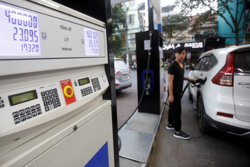 © Reuters. FILE PHOTO: A man pumps petrol for his car at a petrol station in Hanoi