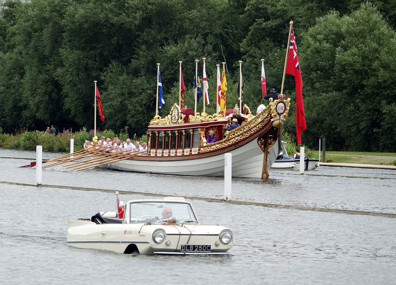 © Reuters. An amphibious car passes Queen Elizabeth II's royal barge Gloriana at the Thames Traditional Boat Festival near Henley-on-Thames