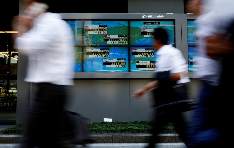 © Reuters. People walk past an electronic board showing Japan's Nikkei average outside a brokerage at a business district in Tokyo