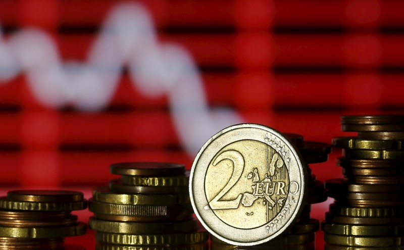 © Reuters. Euro coins are seen in front of a displayed stock graph in this photo illustration taken in Zenica