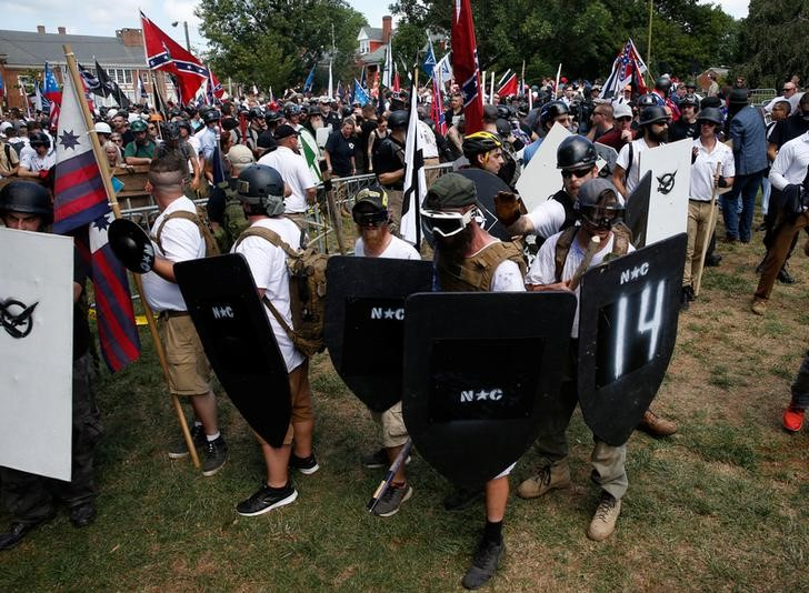 © Reuters. Miembros de grupos nacionalistas blancos sostienen escudos mientras se enfrentan a un grupo de contramanifestantes en Charlottesville