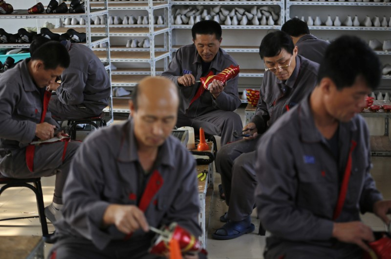 © Reuters. FILE PHOTO - North Korean workers make soccer shoes inside a temporary factory at a rural village on the edge of Dandong