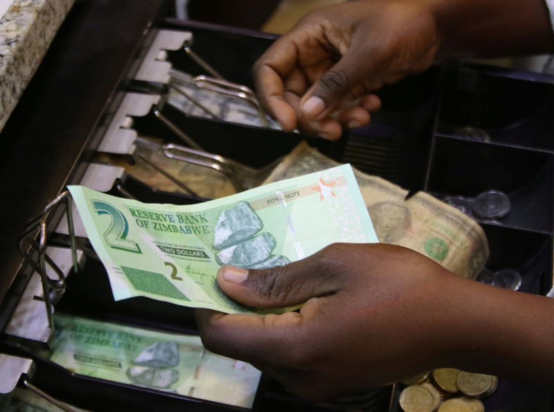 © Reuters. FILE PHOTO: A till operator collects new bond notes from a shopper at a supermarket in the capital Harare