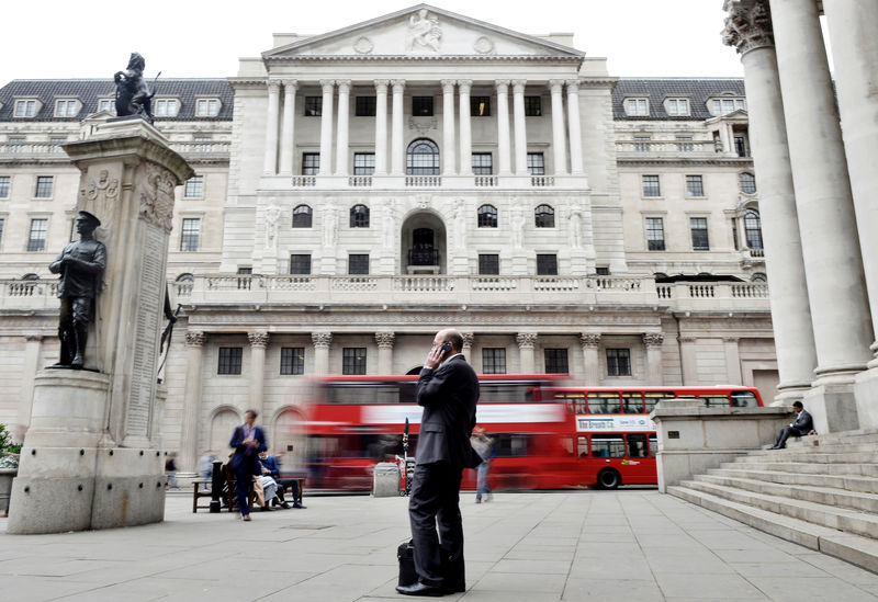 © Reuters. A man talks on a mobile phone as people walk past the Bank of England, in London