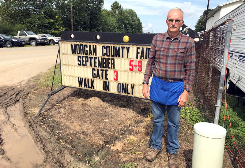 © Reuters. Wilson, 70, stands next to a sign at the Morgan County Fair in McConnelsville