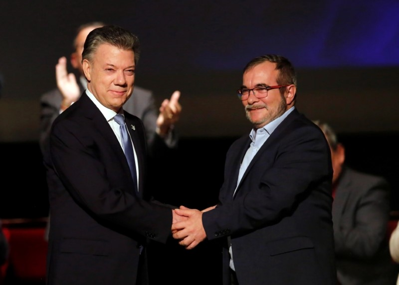© Reuters. Colombia's President Juan Manuel Santos and Marxist FARC rebel leader Rodrigo Londono known as Timochenko shake hands after signing a peace accord in Bogota