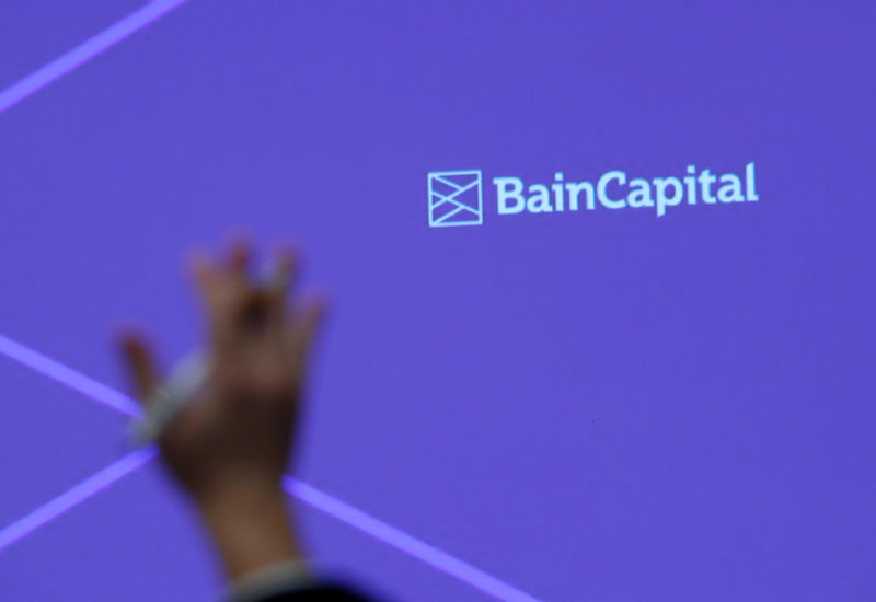 © Reuters. FILE PHOTO: A reporter raises his hand to ask a question during a news conference by Bain Capital LP Managing Director Sugimoto in Tokyo