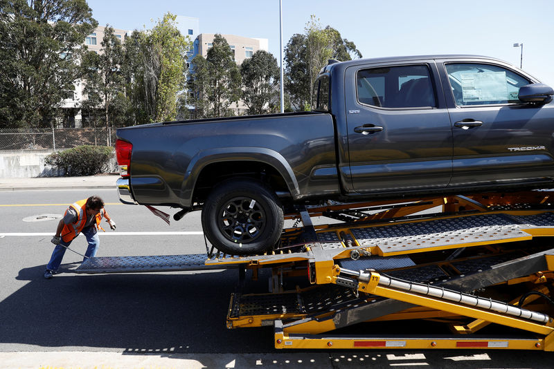 © Reuters. A worker moves a ramp on a car carrier trailer outside City Toyota in Daly City, California
