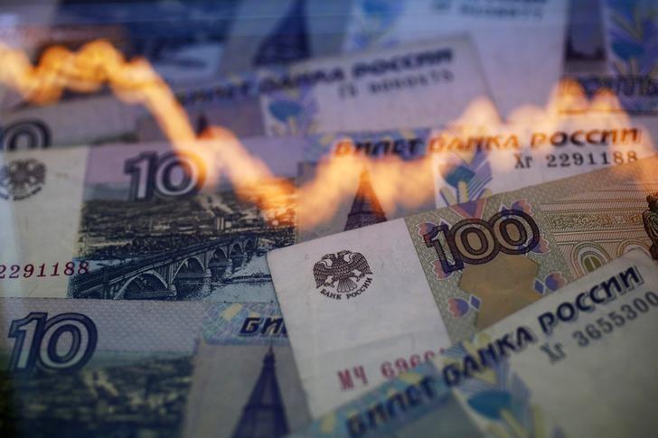 © Reuters. График курса американского доллара к российскому рублю на фоне рублевых банкнот
