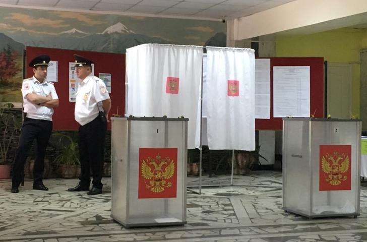 © Reuters. Полицейские на избирательном участке в единый день голосования