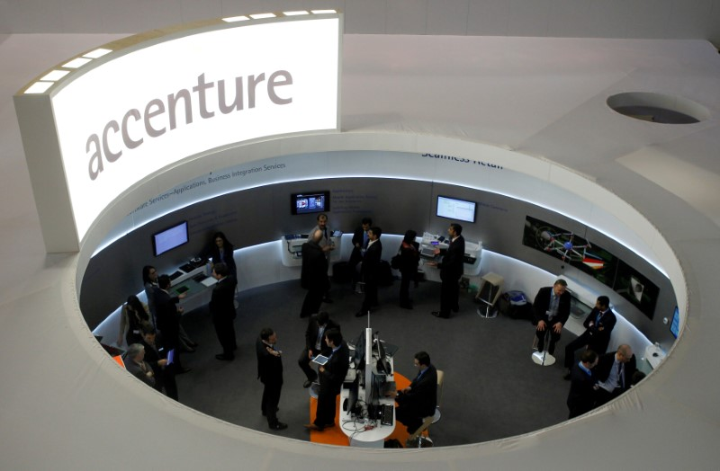 © Reuters. FILE PHOTO: Visitors look at devices at Accenture stand at the Mobile World Congress in Barcelona