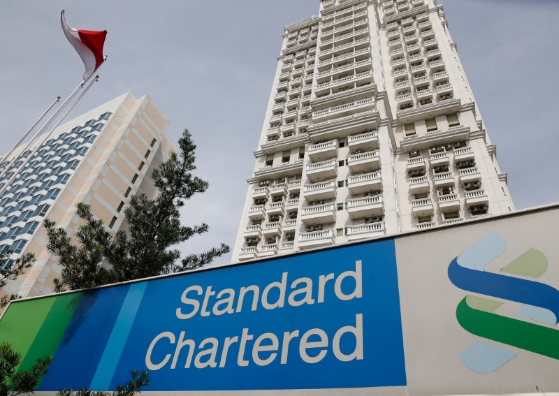 © Reuters. FILE PHOTO: A Standard Chartered sign is seen outside of a building, with a branch of the bank, in Jakarta, Indonesia