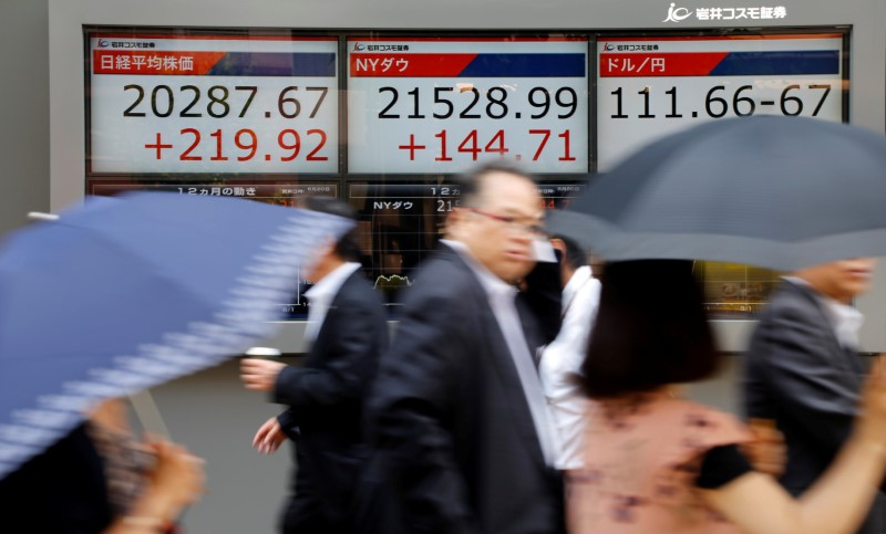 © Reuters. People walk past an electronic board showing Japan's Nikkei average, the Dow Jones average, and the exchange rates between the Japanese yen and the U.S. dollar outside a brokerage in Tokyo