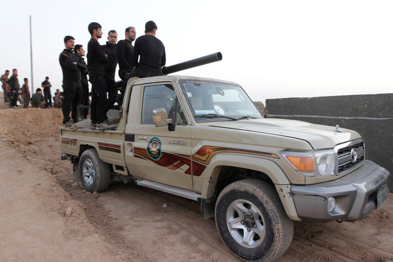© Reuters. Kurdish Peshmerga fighters ride in a vehicule in the Southwest of Kirkuk