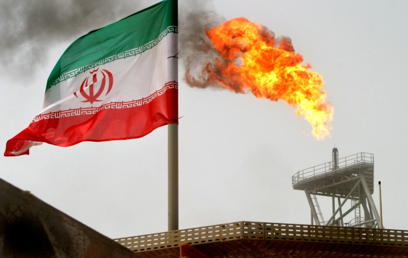 © Reuters. FILE PHOTO: A gas flare on an oil production platform in the Soroush oil fields is seen alongside an Iranian flag in the Gulf