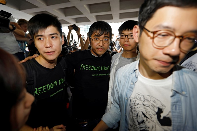© Reuters. Student leaders Lester Shum, Alex Chow, Joshua Wong and Nathan Law hold hands as they walk into the High Court to face verdict on charges relating to the 2014 pro-democracy Umbrella Movement, in Hong Kong