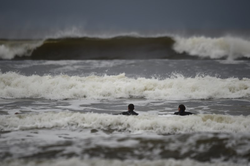© Reuters. Surfers watch as waves approach in the Atlantic on the eve of storm Ophelia in an area where the tide should be out in the County Clare town of Lahinch