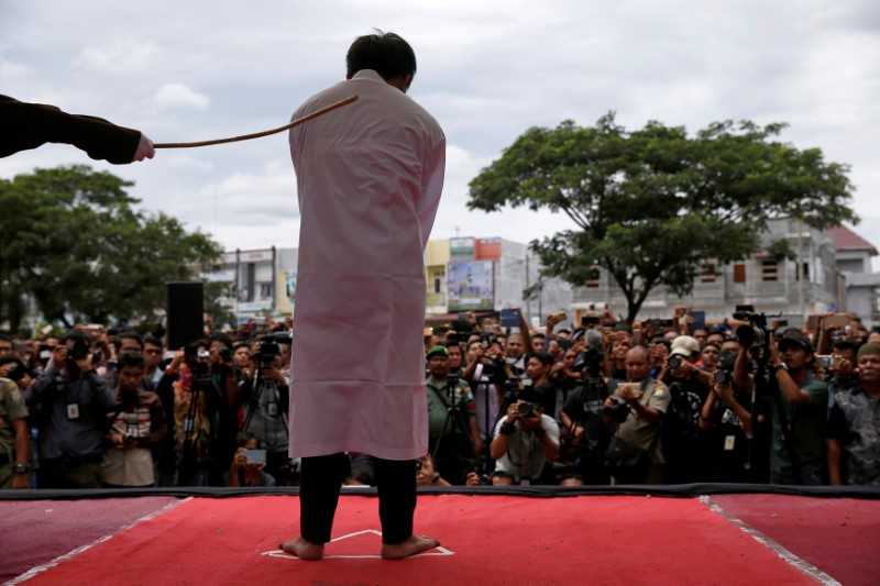 © Reuters. FILE PHOTO: An Indonesian man is publicly caned for having gay sex, in Banda Aceh