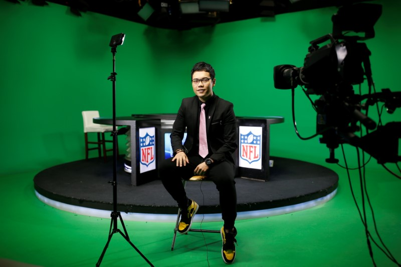 © Reuters. Chinese commentator Wang Zixing poses for a picture after broadcasting a live commentary of a NFL American football game in a studio of the media and gaming firm Tencent Holdings in Beijing