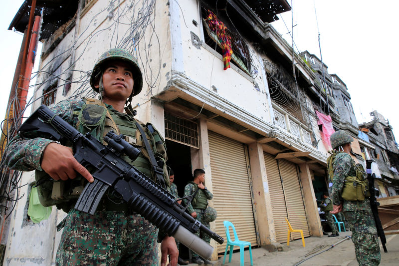 © Reuters. Government soldiers stand guard in front of damaged building and houses in Sultan Omar Dianalan boulevard at Mapandi district in Marawi city