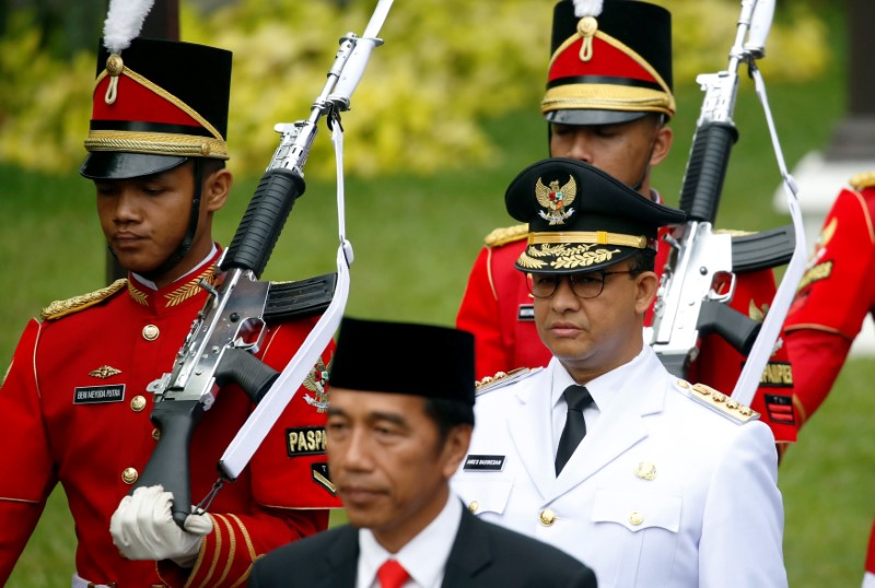 © Reuters. Presidential guards walk with Indonesia President Joko Widodo and Jakarta Governor Anies Baswedan for a swearing-in ceremony at the Presidential Palace in Jakarta