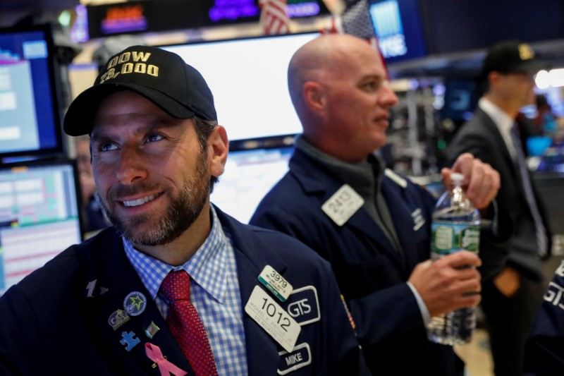 © Reuters. Specialist trader Michael Pistillo Jr. wears a Dow 23,000 hat at his post on the floor of the NYSE in New York