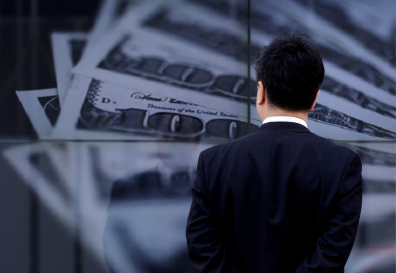 © Reuters. FILE PHOTO: A businessman looks at a screen displaying a photo of U.S. 100 dollar bank notes in Tokyo