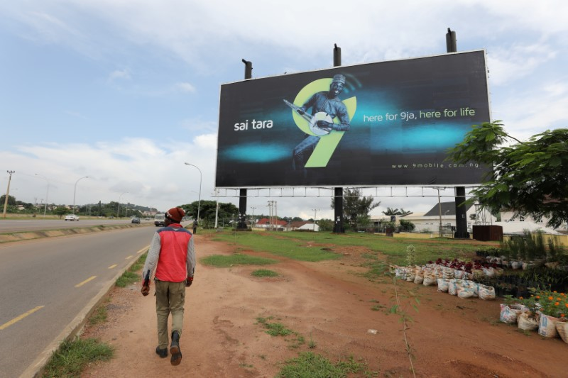 © Reuters. FILE PHOTO: A man walks towards a 9 Mobile telecom company outdoor billboard in Abuja