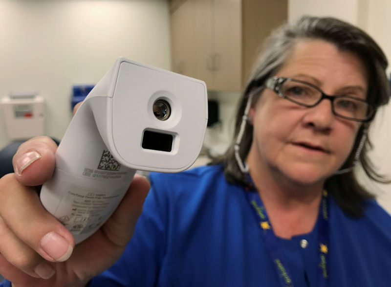 © Reuters. Registered nurse Tara McCormick, Clinical Services Manager, demonstrates an infrared thermometer at West Virginia University Hospital in Morgantown