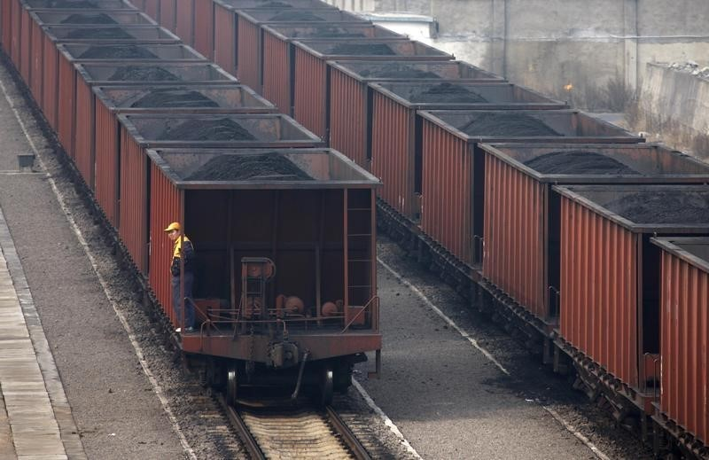 © Reuters. FILE PHOTO: A worker stands on a wagon of a coal train as it tranfers coal to a power plant in Huaibei