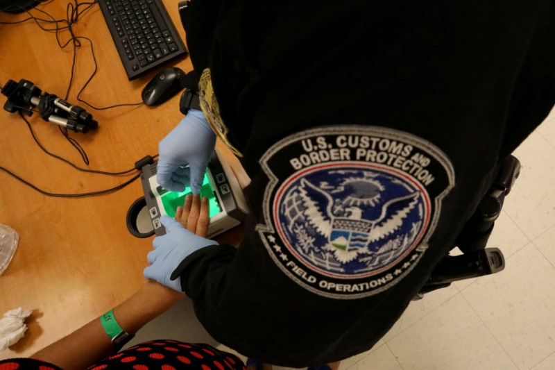 © Reuters. FILE PHOTO: A woman who is seeking asylum has her fingerprints taken by a U.S. Customs and Border patrol officer at a pedestrian port of entry from Mexico to the United States