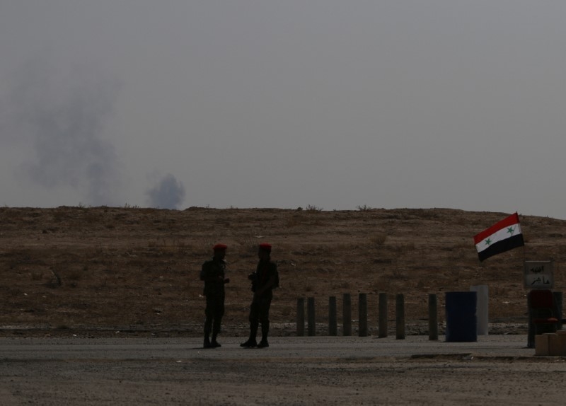 © Reuters. Smoke rises as Syrian army soldiers stand near a checkpoint in Deir al-Zor