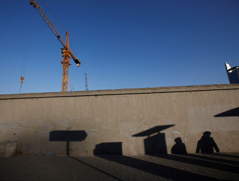 © Reuters. FILE PHOTO: Pedestrians cast their shadows  on a wall at a construction site in Beijing