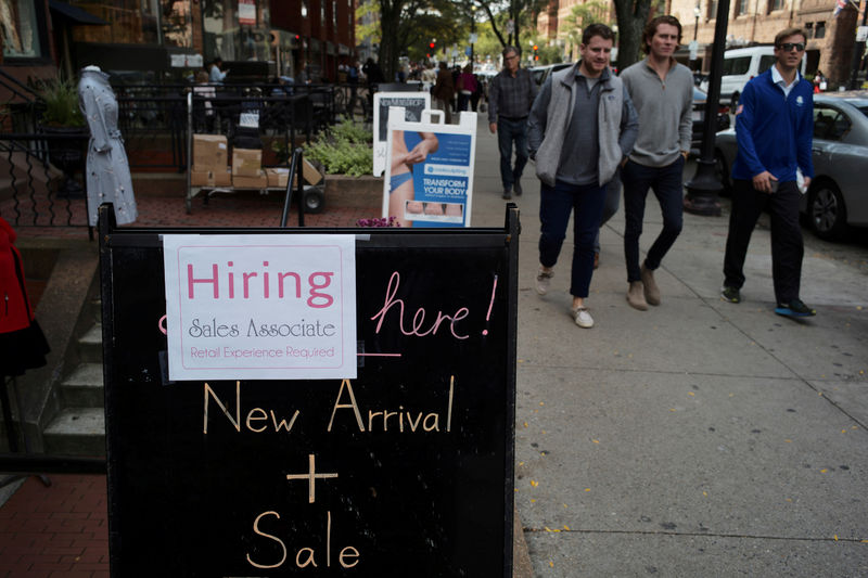 © Reuters. FILE PHOTO: Pedestrians pass a sign advertising a sale and a job opening at a shop on Newbury Street in Boston