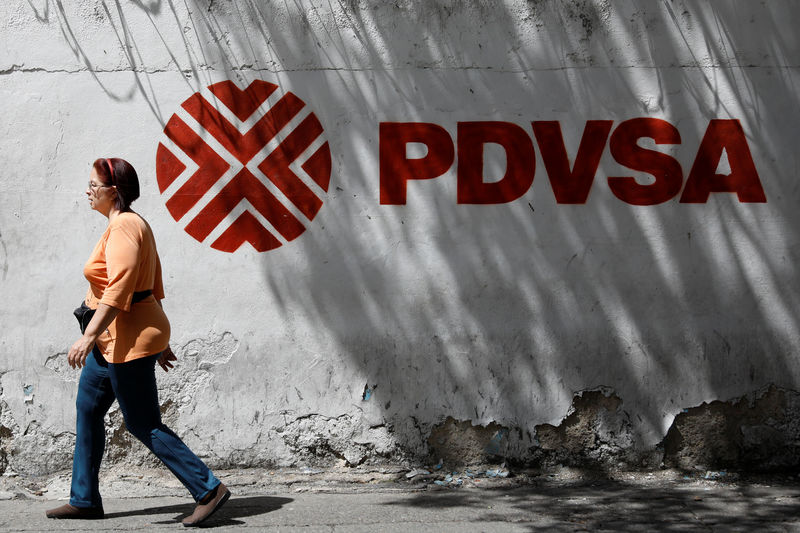 © Reuters. A woman walks past a mural with the corporate logo of the state oil company PDVSA in Caracas