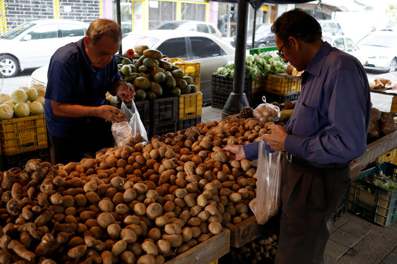 © Reuters. People select potatoes at a street market in Caracas