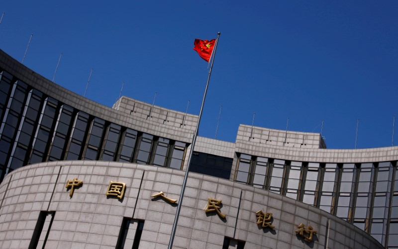 © Reuters. FILE PHOTO:  A Chinese national flag flutters outside the headquarters of the People's Bank of China, the Chinese central bank, in Beijing, China
